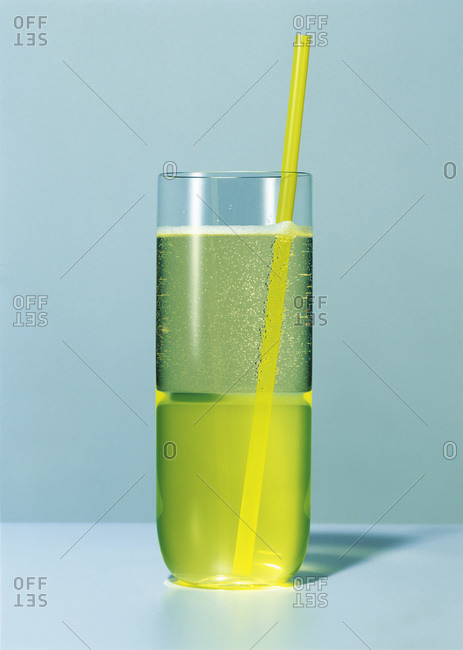 Studio shot of a glass of sparkling wine with a straw