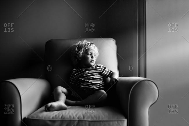 A blonde boy sitting on an armchair