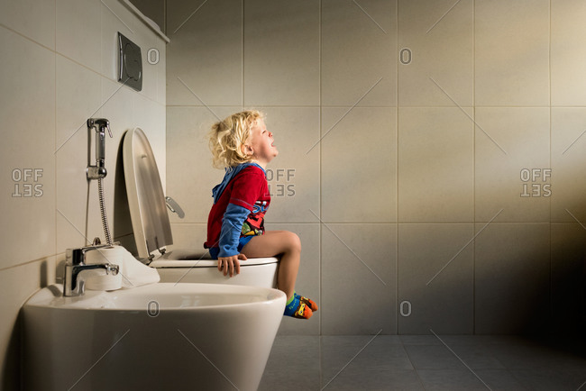 A little boy cries on the toilet