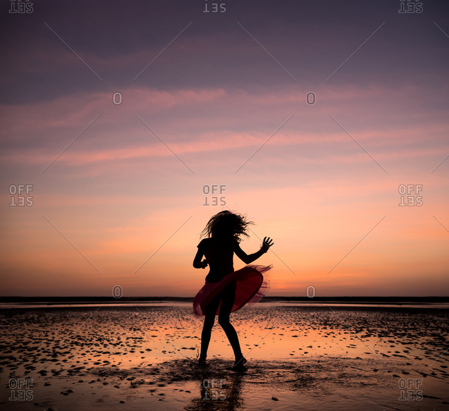A little girl dances on the beach at sunset