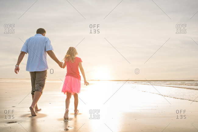 A father and his daughter hold hands on the beach