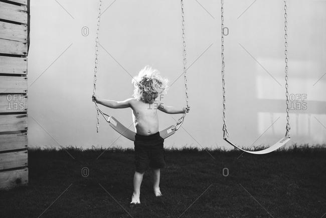 A little boy holds onto a swing