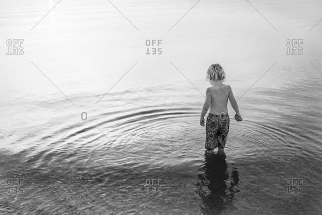A little boy wades into the ocean