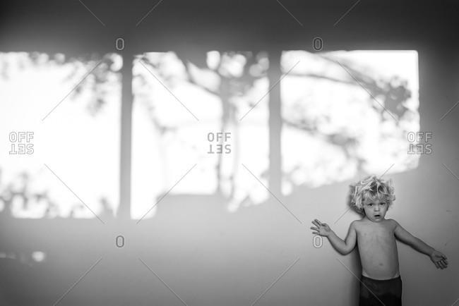 A little boy leans against a white wall