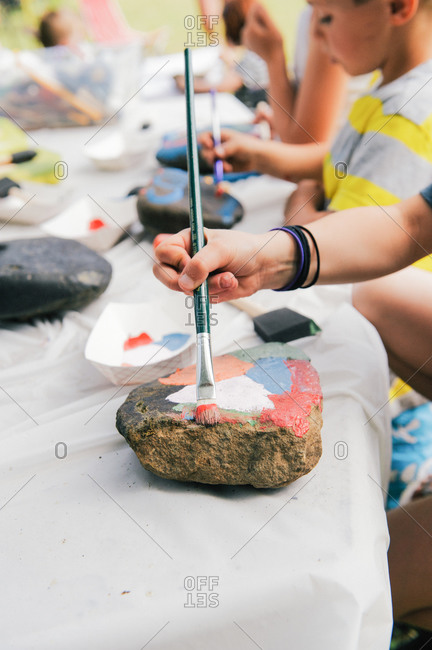 Kids painting rocks at a table