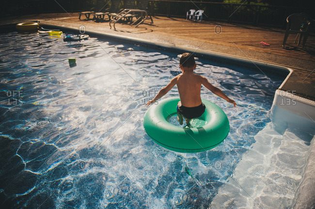 Boy jumping into ring toy in swimming pool