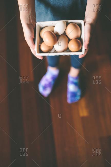 Boy holding fresh basket of eggs in home