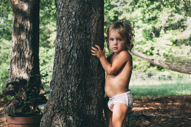 A little girl holds a tree trunk