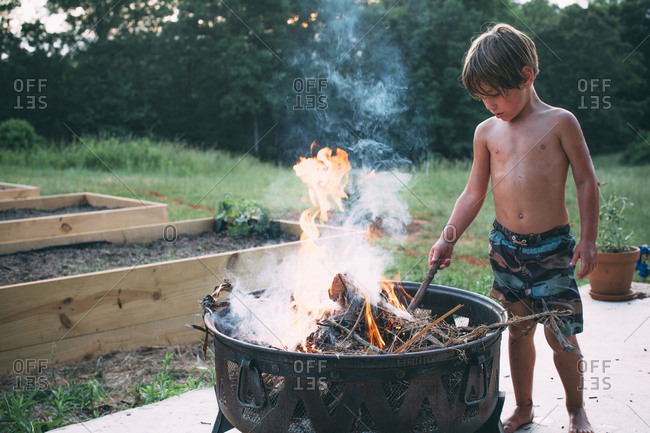 A boy tends to a fire on a back patio