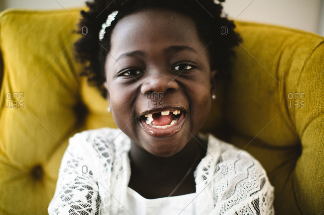 A little girl laughs while chewing gum