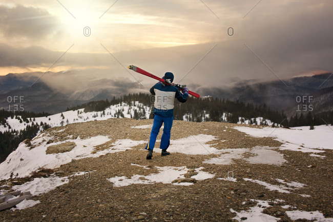 Man with skis overlooking snowy pine mountains