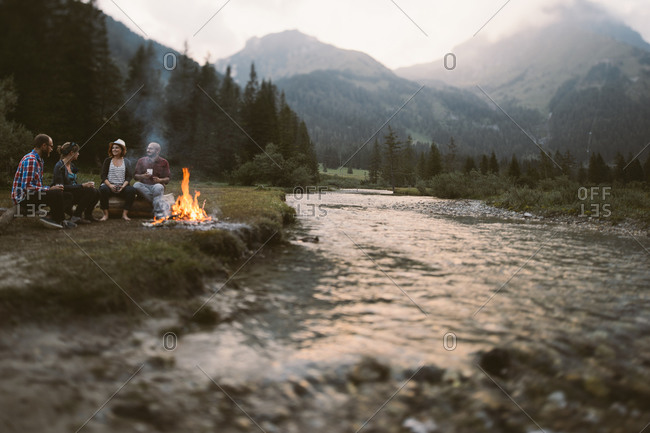 Friends sitting around a campfire next to a river