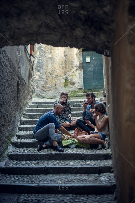 Four friends enjoy some snacks in an old stairwell
