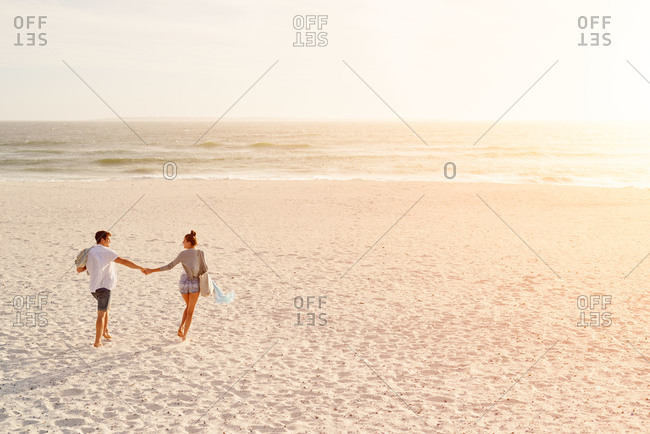Young couple holding hands walking towards sunset on empty beach