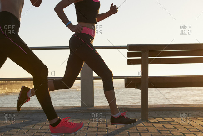 Two female athletes running using fitness tracker wearable devices