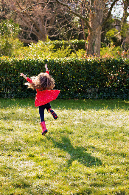 A little girl in a red dress leaps in the air