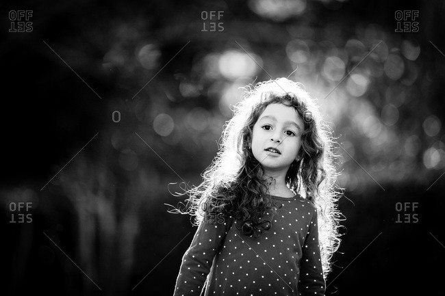A little girl stands in the sunlight