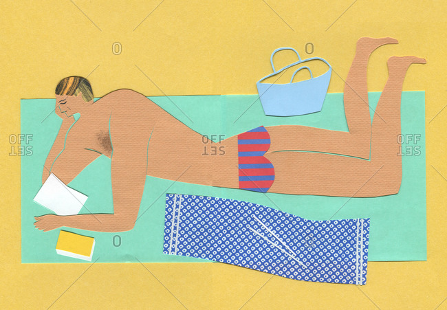 Man in swim trunks with book on beach