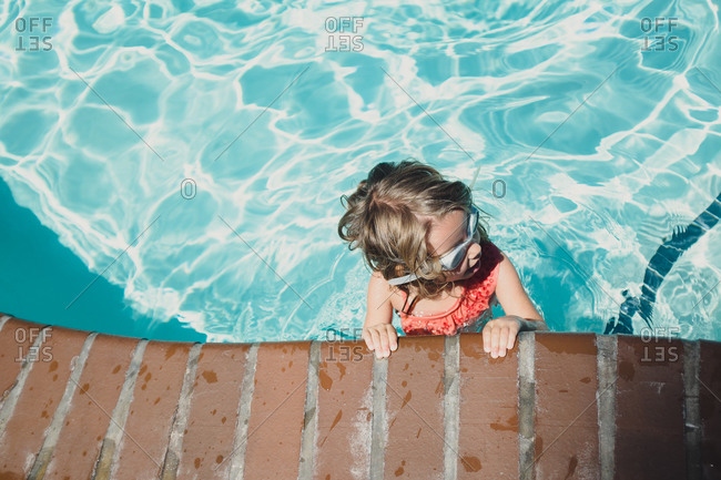 Girl at side of pool in goggles
