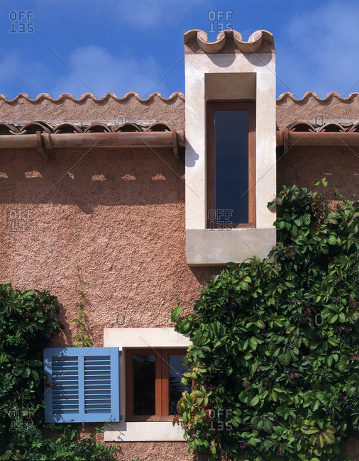 Mallorca, Spain - August 28, 2014: Square and rectangular windows on a Spanish style villa exterior with plants growing on the wall