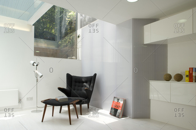 London, England, UK - March 3, 2009: Black upholstered chair and ottoman set under a skylight in a modern room