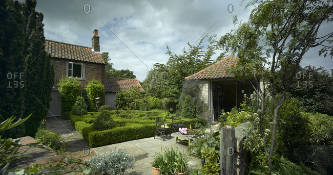 London, England, UK - May 20, 2015: A home in Lincolnshire with a knot garden and mature shrubs, and paving
