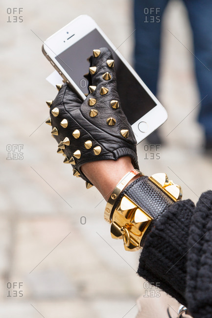 London, England - February 28, 2015: London Fashion Week attendee wearing a spiked leather glove and holding a phone