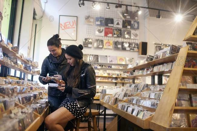 Hip couple browsing in record store