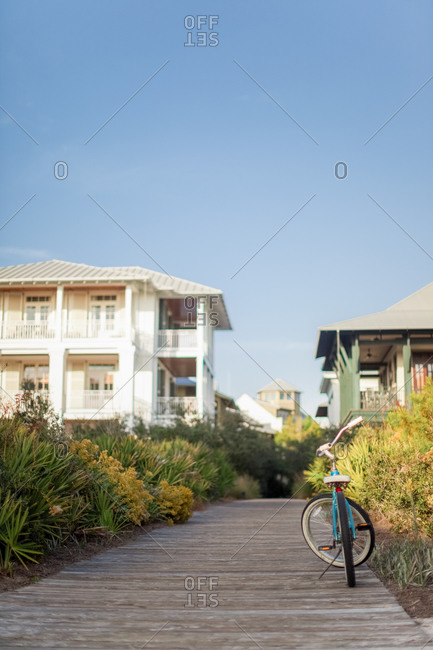 Bicycle parked on a beach path that runs between houses