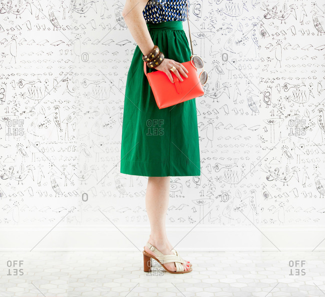 Woman in retro styled skirt and shoes standing against whimsical bird wallpaper