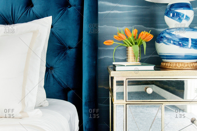Close up of a bed with blue velvet headboard and mirrored night table