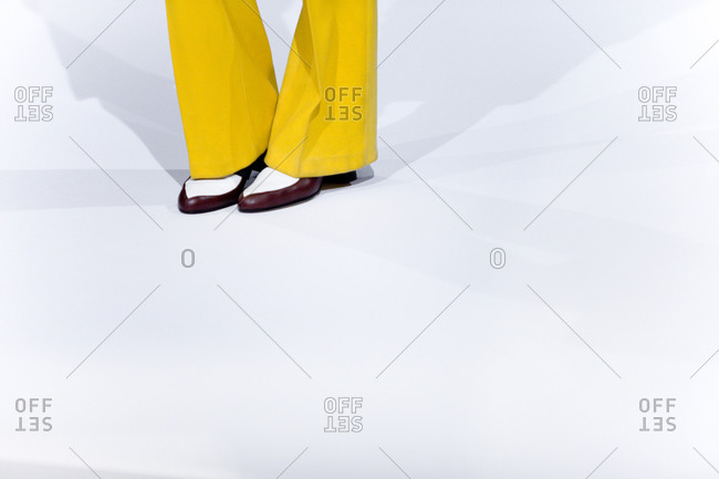 Close up of bright yellow trousers with menswear-inspired shoes