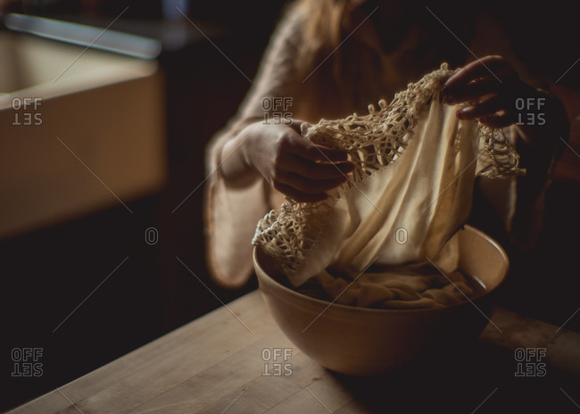 Hands washing a delicate lace scarf in bowl of water
