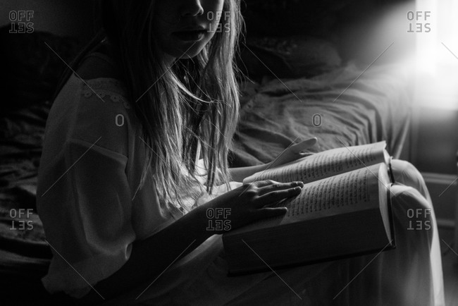 Young girl reading a Hebrew text on bed