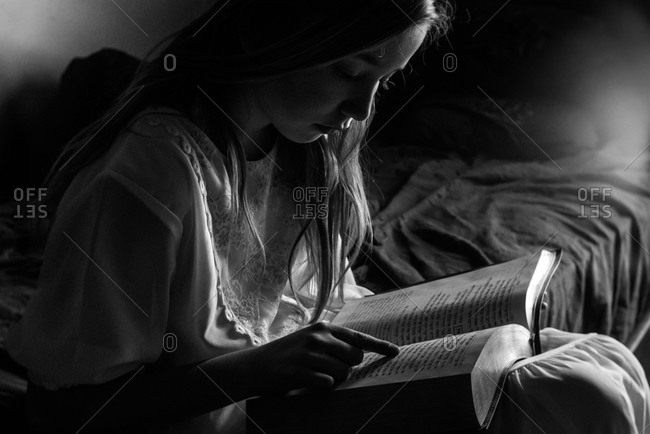 Portrait of a young girl reading Hebrew text on bed