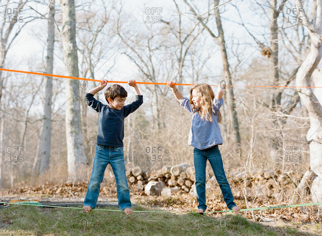 Two young children balancing on a slackline in their backyard