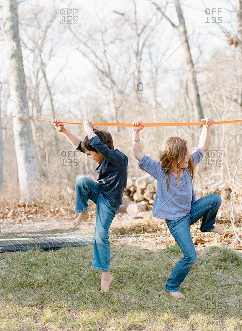 Brother and sister climb onto a slackline in their backyard