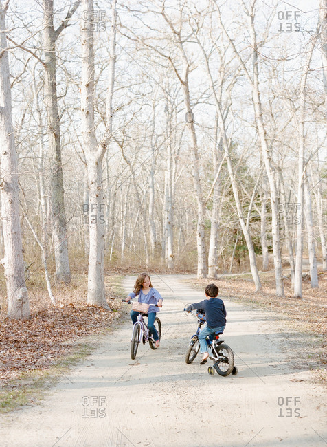 Two children riding on bicycles on forest path