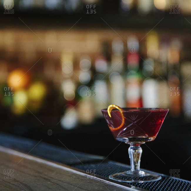 A cocktail on the edge of a bar