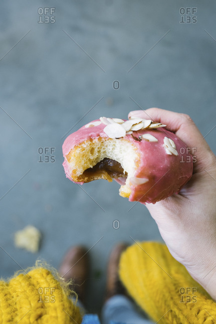 A fruit-filled donut with pink frosting