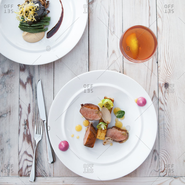 A duck dish next to a plate with bison