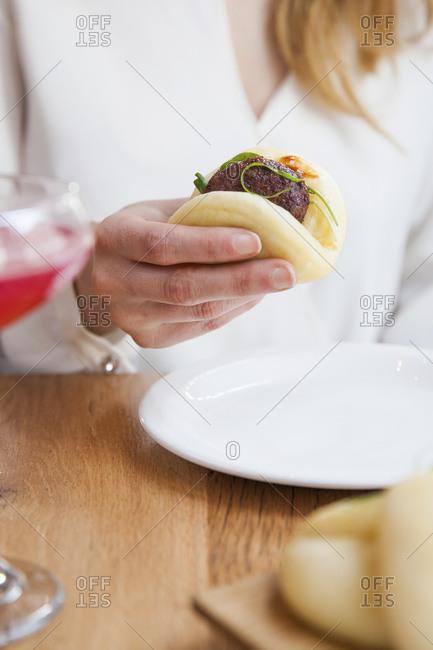 A woman eats a meatball bao
