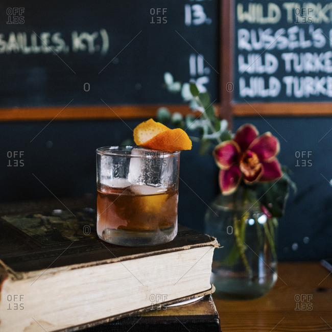 An old fashioned cocktail on a stack of vintage books