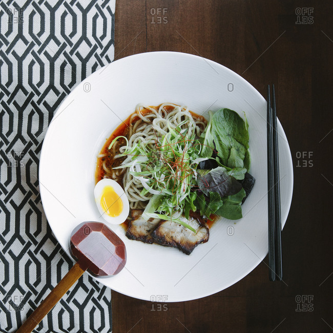 A bowl of ramen noodles with pork and an egg half