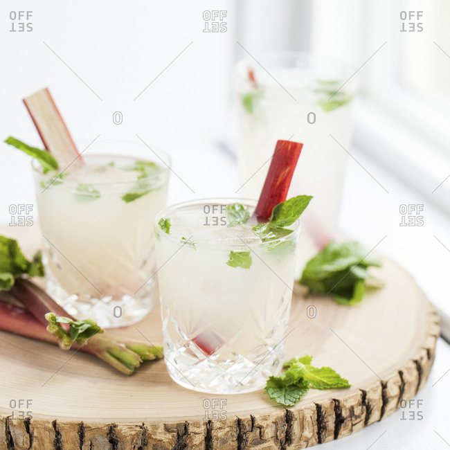 Three rhubarb mojitos on a wood tray