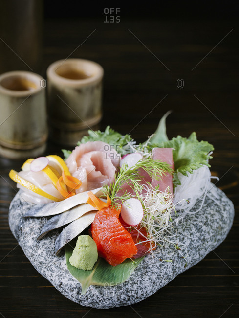 A variety of sashimi served on a stone rock