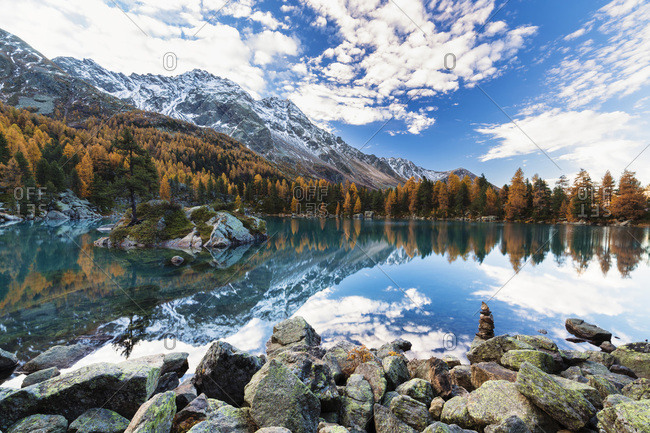 Cairn by Lago di Saoseo surrounded by European larch trees in autumn