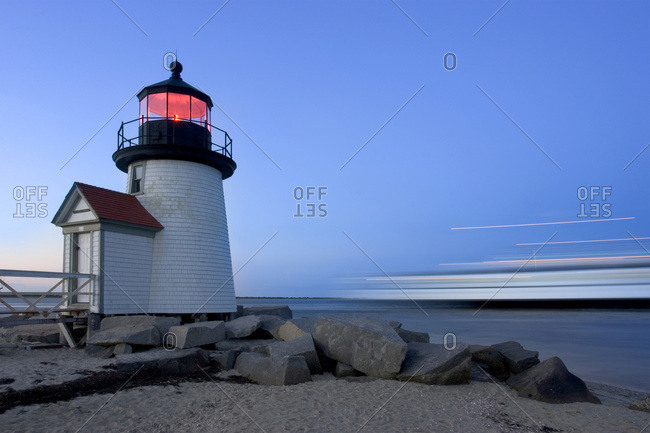 The Brandt Point Lighthouse illuminated at dusk as a ferry passes by