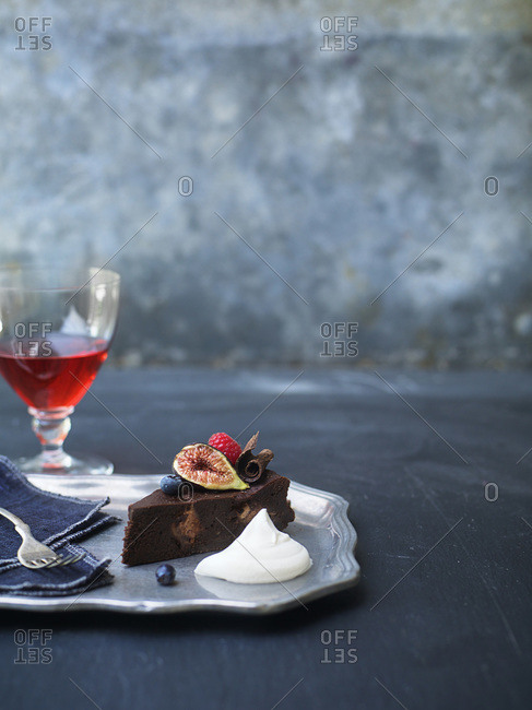 Glass of red wine and fruit topped torte with dollop of whipped cream