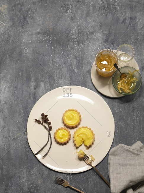 Overhead view of lemon tarts on white plate with candied lemons
